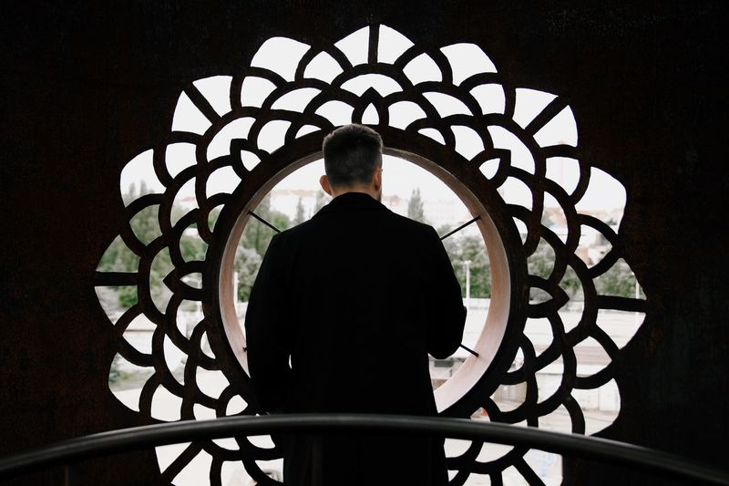 Rear view of silhouette man standing against building