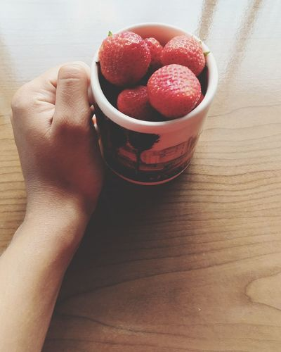 Cropped hand holding strawberries in cup on table