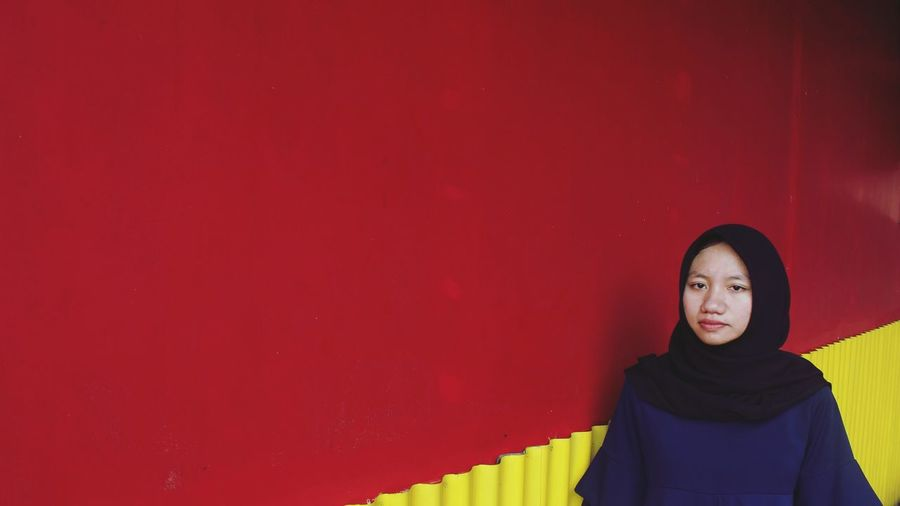 Portrait Of Smiling Young Woman By Red Wall