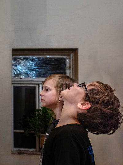 Side view portrait of two boys standing against wall at home