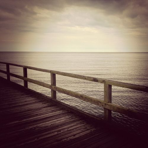 Cropped wooden jetty along calm sea