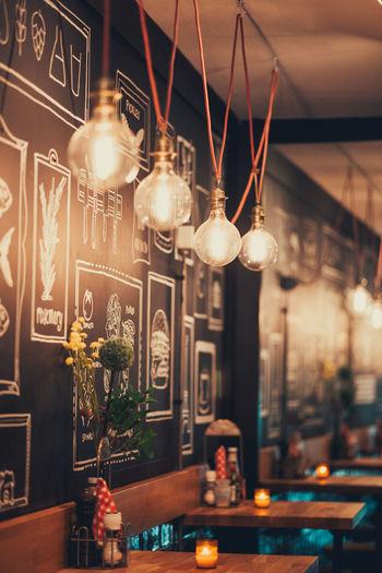 Illuminated light bulbs hanging in restaurant