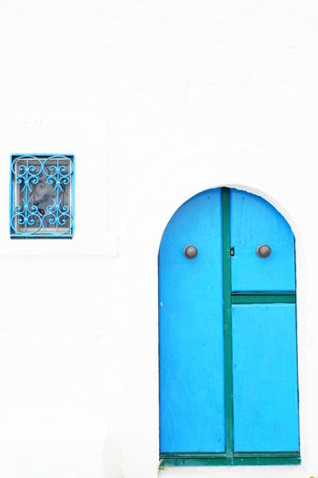 Blue Door And Window Blue On White Blue Wooden Door Building Exterior Contrasting Colours Lines And Shapes No People Outdoors Semicircular Doorframe White Background