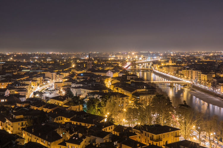Illuminated cityscape by adige river against sky at night