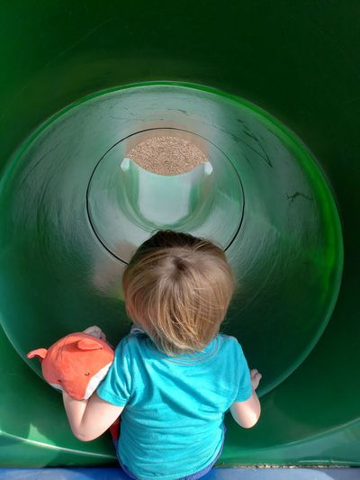Rear view of boy playing in tunnel slide