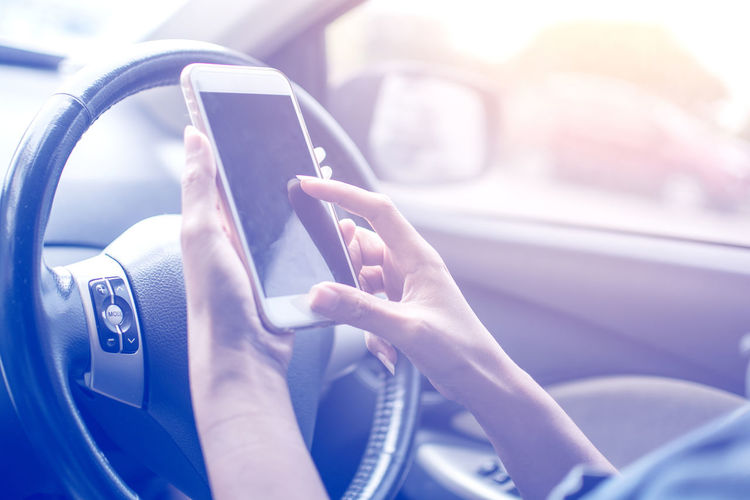Cropped hand of woman using mobile phone in car