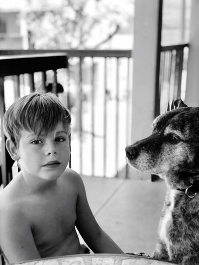 Portrait of shirtless man with dog looking away