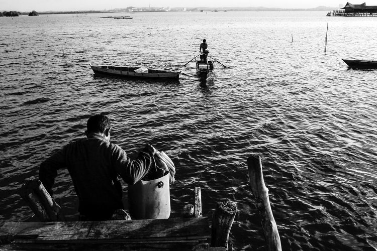 Rear view of men on boat in sea