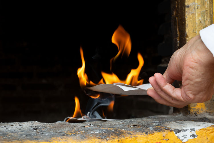 Cropped hand of man burning paper