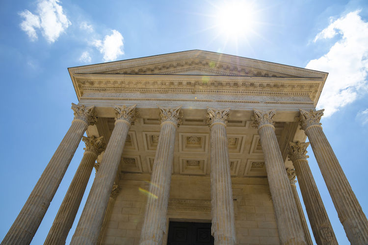 "Maison Carrée (French for ""square house"") is an ancient building in Nîmes, one of the best preserved Roman temple facades to be found in the territory of the former Roman Empire Low Angle View Architecture Sky Architectural Column Built Structure Cloud - Sky Sunlight Sunbeam History The Past Day Travel Destinations Building Exterior Lens Flare No People Ancient Civilization Neo-classical Archaeology Temple - Building Roman Antique Façade Front View Pillars Ancient Rome 17.62°"