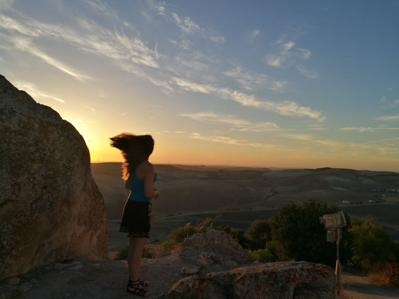 sky, sunset, one person, real people, leisure activity, lifestyles, standing, cloud - sky, full length, beauty in nature, rock, scenics - nature, side view, rock - object, nature, mountain, women, solid, non-urban scene, outdoors, looking at view