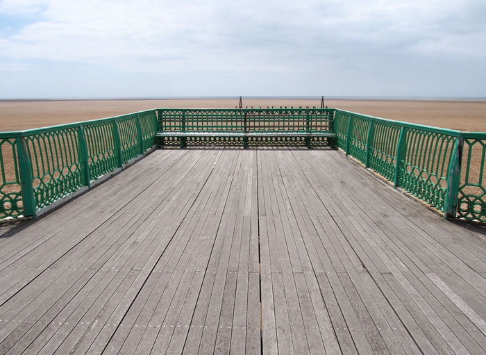 View of wooden pier leading towards sea against sky