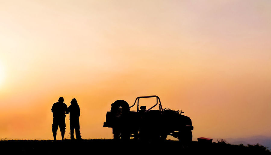 Silhouette Friends With Car On Field Against Clear Sky During Sunset