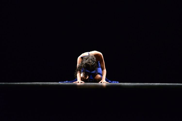 Woman kneeling on floor against black background
