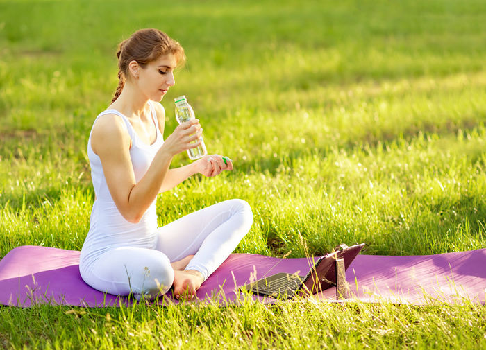 Woman drinking water while exercising in park