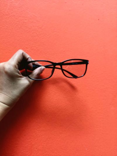 Cropped hand holding eyeglasses against red wall