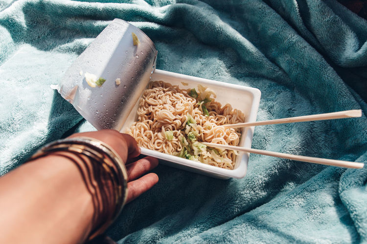 Midsection of person holding instant noodles yakisoba on light blue blanket at home