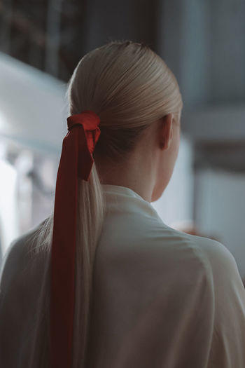 Female hairstyle of blonde hair elegant ponytail with red ribbon. back view