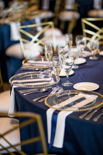 Champagne flutes and plates on table in restaurant