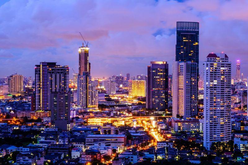 Illuminated city against cloudy sky at dusk
