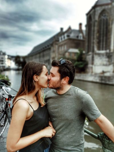 Young Couple Kissing While Standing In City