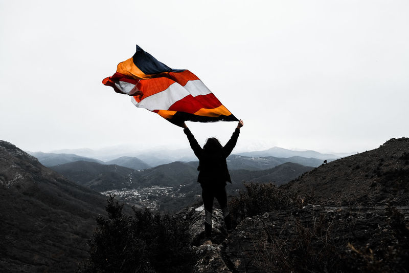 Woman with flag standing on mountain against clear sky