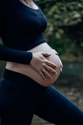 Midsection of pregnant woman touching belly while standing outdoors