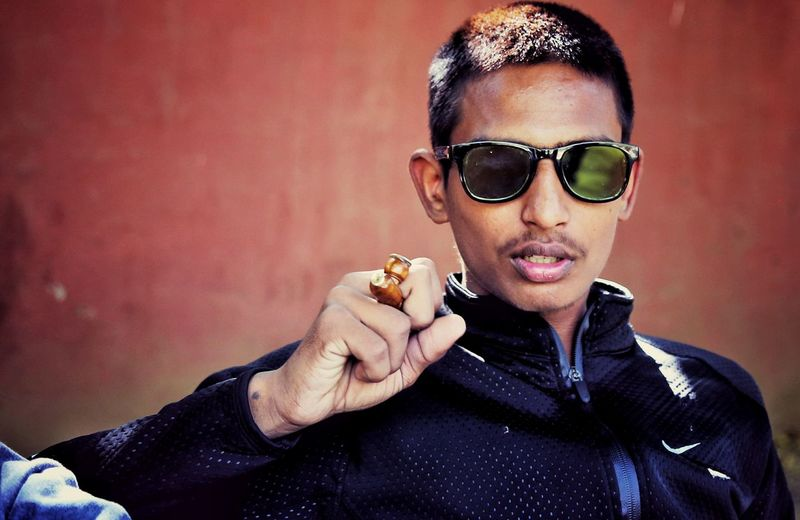 Young Man With Smoking Pipe Wearing Sunglasses Against Wall