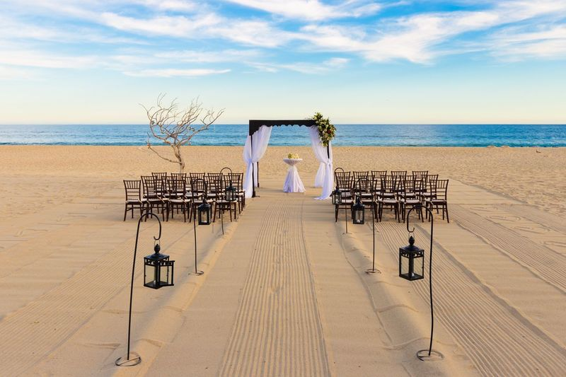 Chairs and decoration at beach against sky
