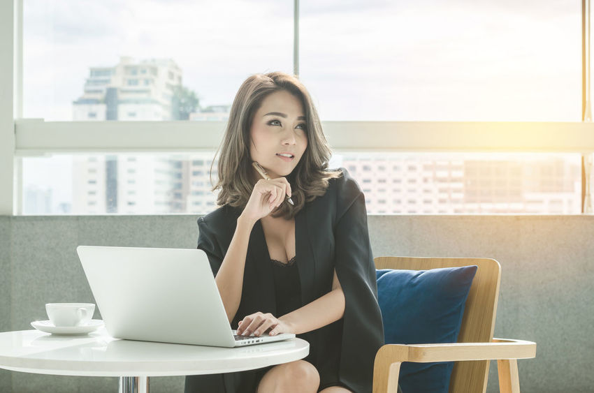 Business Businesswoman Communication Computer Connection Convenience Day Desk Front View Holding Indoors  Laptop Office One Person Portability Real People Sitting Table Technology Using Laptop Window Wireless Technology Women Young Adult Young Women