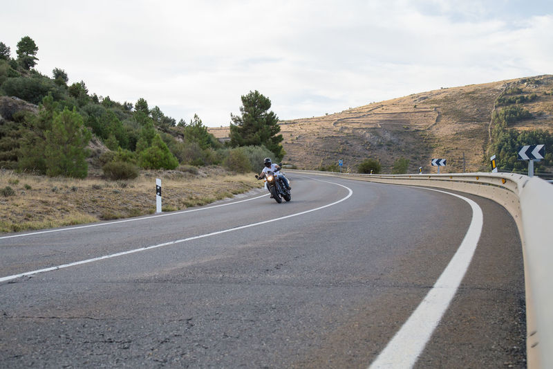 Young Man Riding Motorcycle On Road Against Cloudy Sky