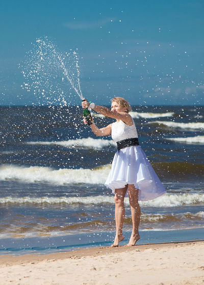 Woman splashing champagne at beach against clear sky
