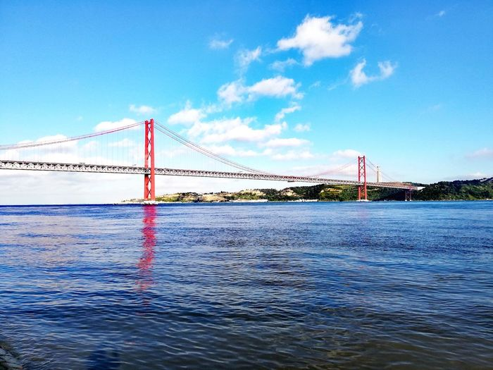 Looking along the River Tejo towards the 25 de Abril Bridge, Lisbon. Portugal. River Portugal Travel Tourism Europe Almada EyeEm Selects Water Sea Blue Sky Cloud - Sky Windsurfing Kiteboarding Aquatic Sport Paddleboarding Paddling Shore Buoy Sailboat Water Sport Mast