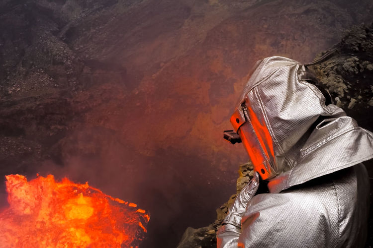 High angle view of person wearing protective workwear by volcano