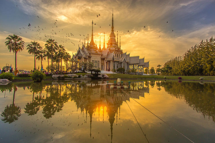 Temple of the evening in Thailand Sky Architecture Water Built Structure Building Cloud - Sky Tree History No People Outdoors Spire  Sunset Building Exterior Temple - Building Thailand Photos Landmark Building Noise Art Blured Moments Overlighting Reflections In The Water Art Arts Culture And Entertainment Thai EyeEmNewHere