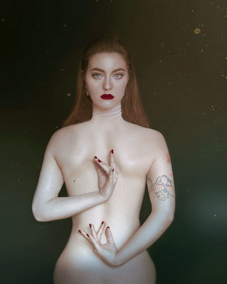 Digital Composite Image Of Topless Beautiful Young Woman Standing Against Black Background