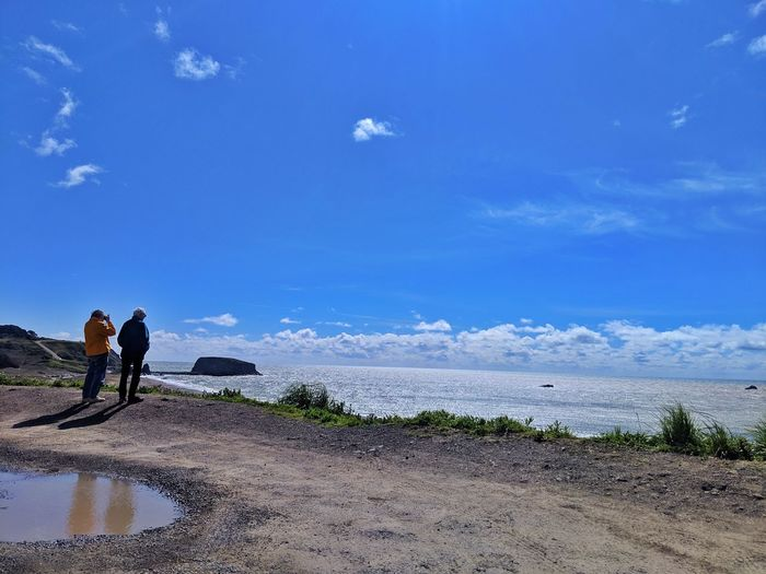 People on Overlook by ocean. Man Woman Couple People Coat Windy Ocean Dirt Soil Overlook Aerial View Below Above Turnout Puddle Water Gravel Curving Blue Sky Background Water Full Length Working Occupation Beach Standing Sea Sky Cloud - Sky Wave