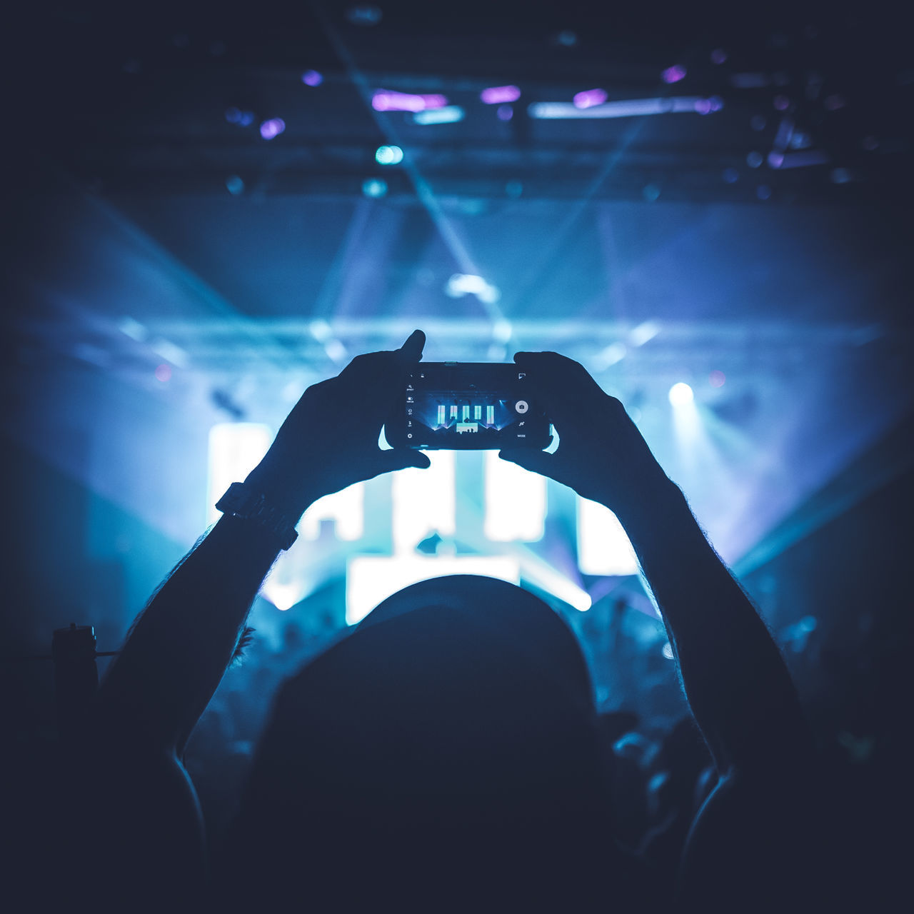 Cropped Hand Photographing Using Smart Phone In Music Concert