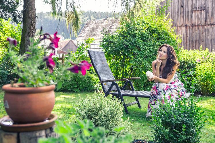 Thoughtful Woman Sitting On Lounge Chair In Yard