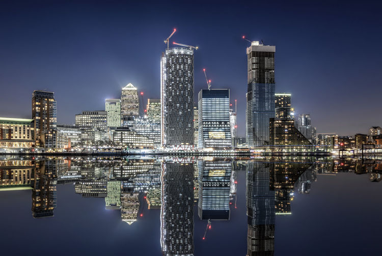 The financial district of London, UK, Canary Wharf, with reflections in the Thames river Architecture Building Exterior Water Waterfront Reflection Building Skyscraper Tall - High City Illuminated Tower Symmetry Financial District  Modern Night Office Building Exterior Cityscape London Canary Wharf Lights Built Structure Travel Destinations Money Construction United Kingdom