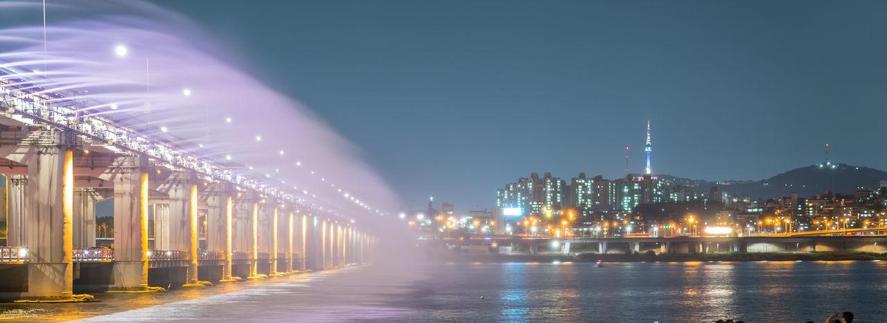 Moonlight Rainbow Fountain On Banpo Bridge Over Han River Against Clear Sky At Dusk