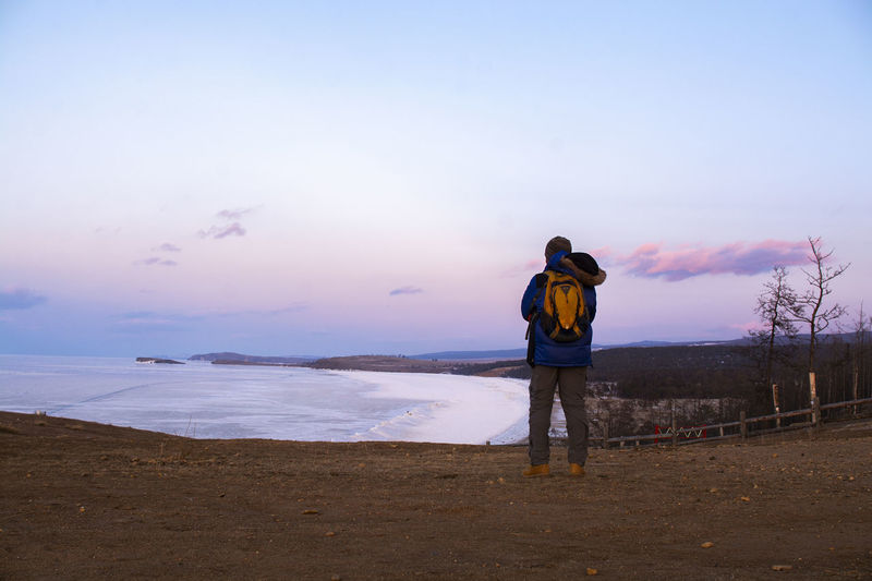 Lake Bikal, Russia Rear View Sky One Person Real People Leisure Activity Land Beauty In Nature Scenics - Nature Full Length Lifestyles Standing Beach Men Tranquility Tranquil Scene Sunset Activity Nature Cloud - Sky Outdoors Warm Clothing Looking At View Hood - Clothing