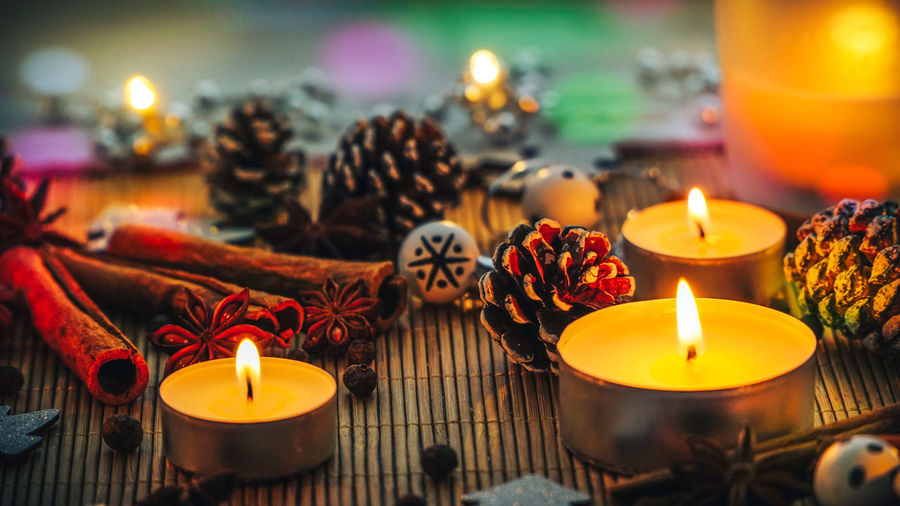Close-up of burning tea lights decorations and spices on table