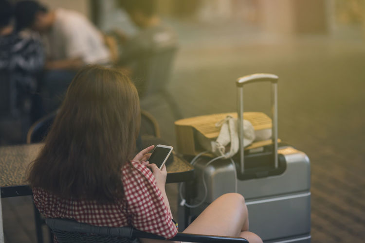 Woman using mobile phone while sitting on seat