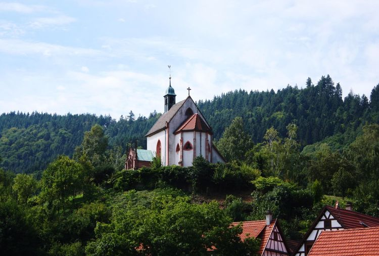 Low angle view of church on green mountain against sky
