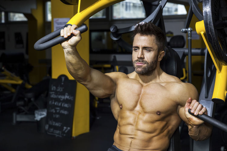 Man exercising on equipment at gym