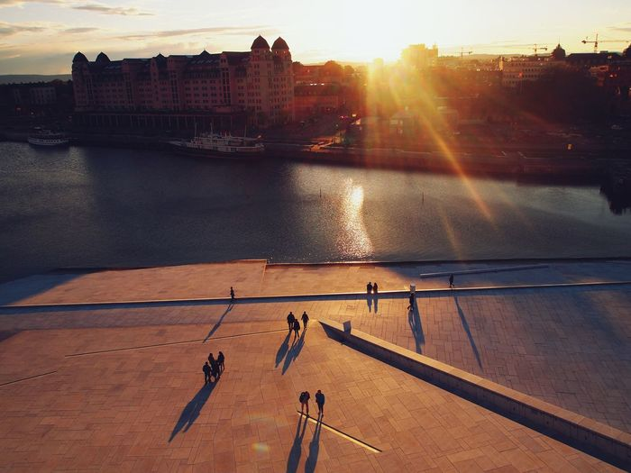 High angle view of people by river in city against sky