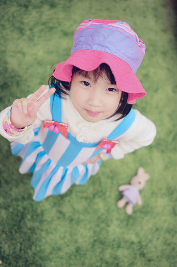 High angle portrait of girl gesturing peace sign on field