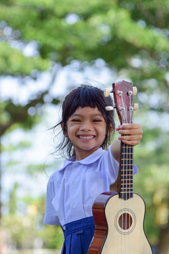 Portrait of smiling girl holding ukulele while standing against trees