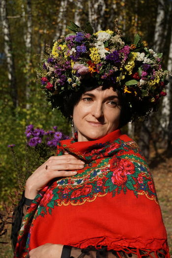 Woman looking away while wearing flowers against trees